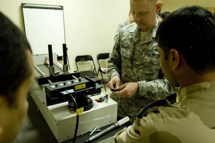 Офицер армии США проверяет качество детали